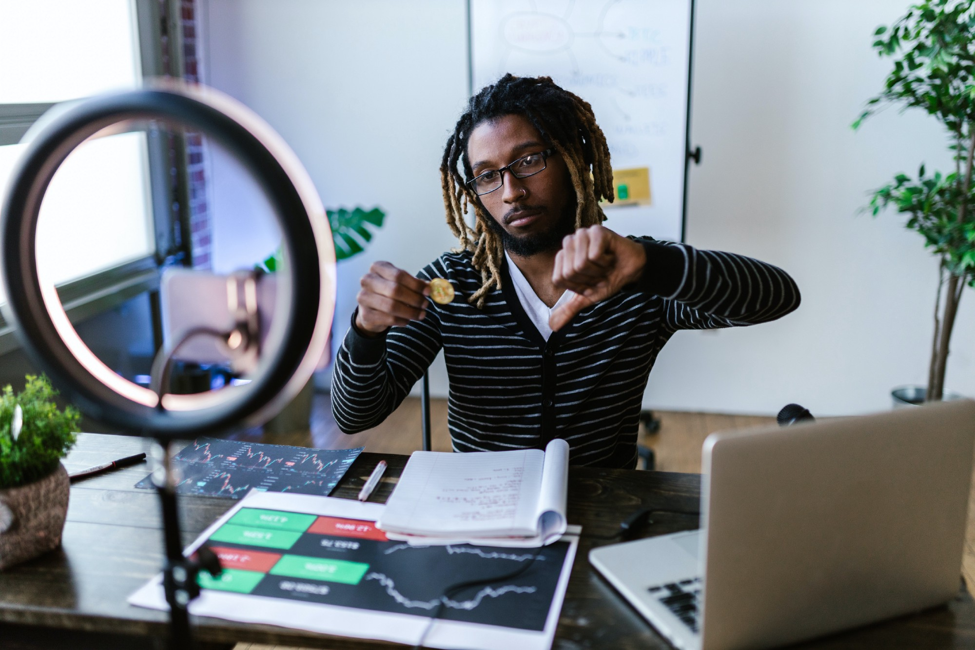 Man with a video set up is holding a physical Bitcoin and giving a thumbs-down sign in front of a desk with papers, graphs, laptop, ring light, etc.