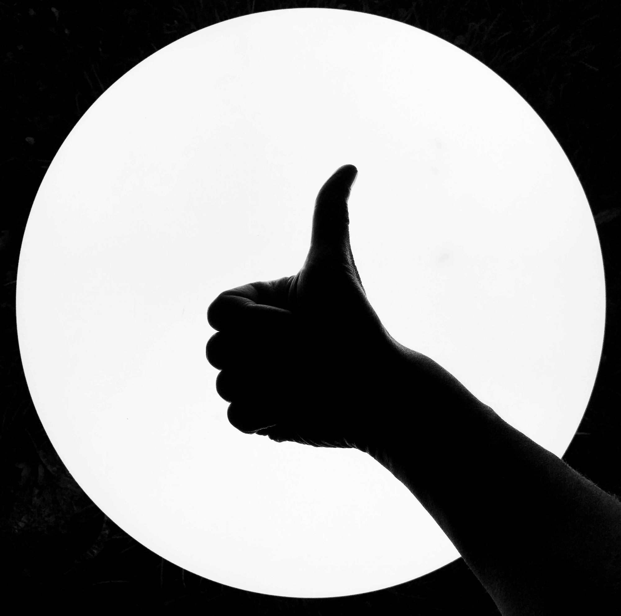 Silhouette of a man's thumb pointing up.