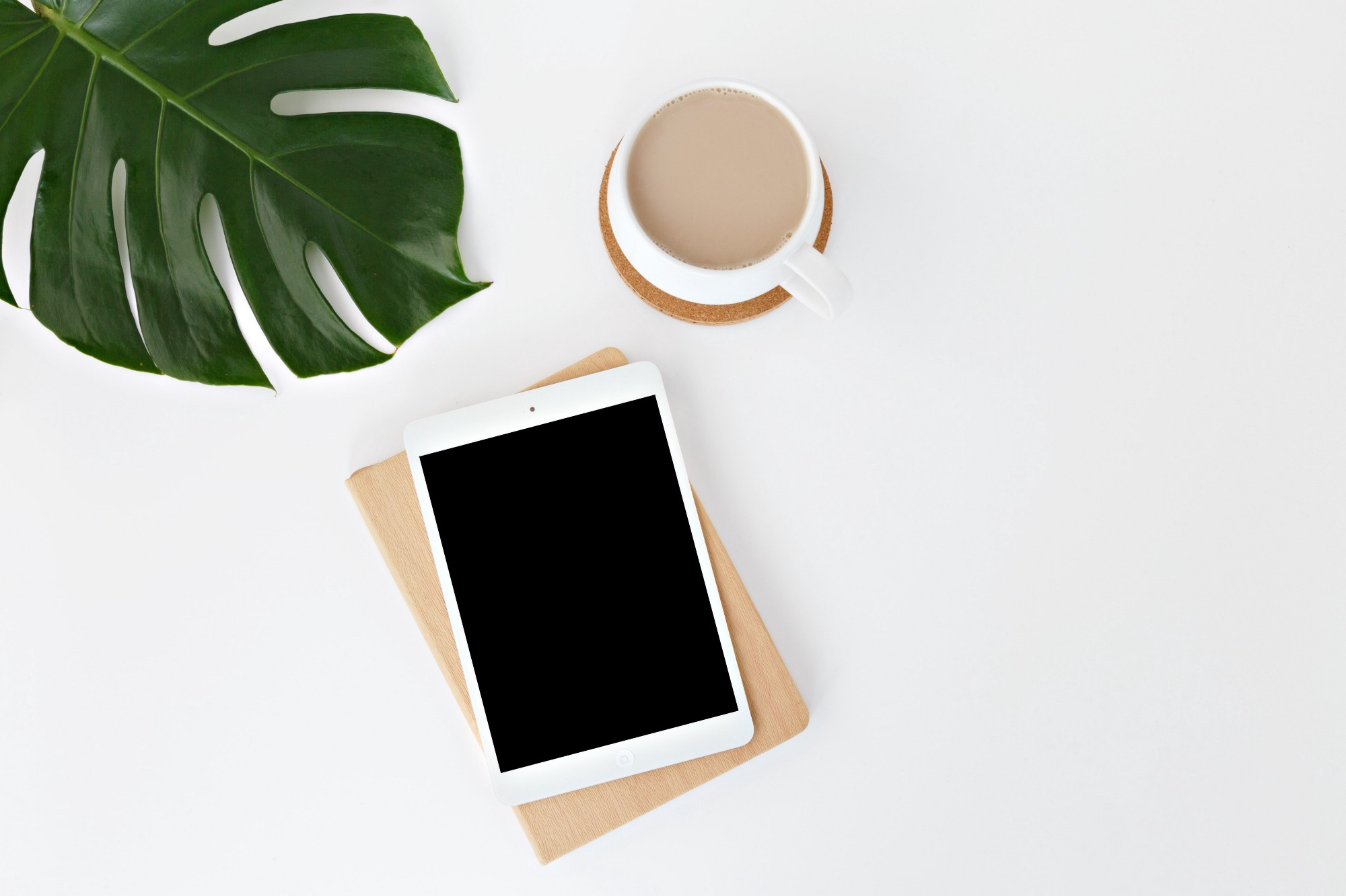 An iPad and Cup of Coffee sit on a desk, beside a plant.