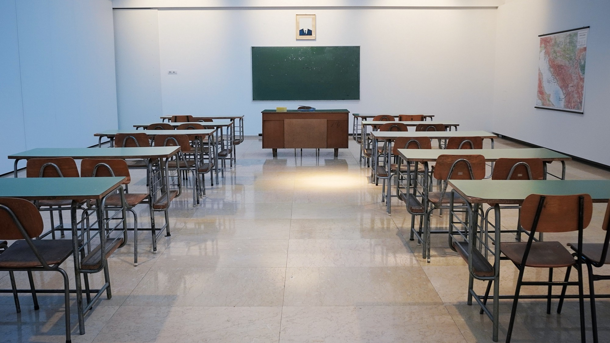 Empty classroom with wooden desks and a green chalkboard.