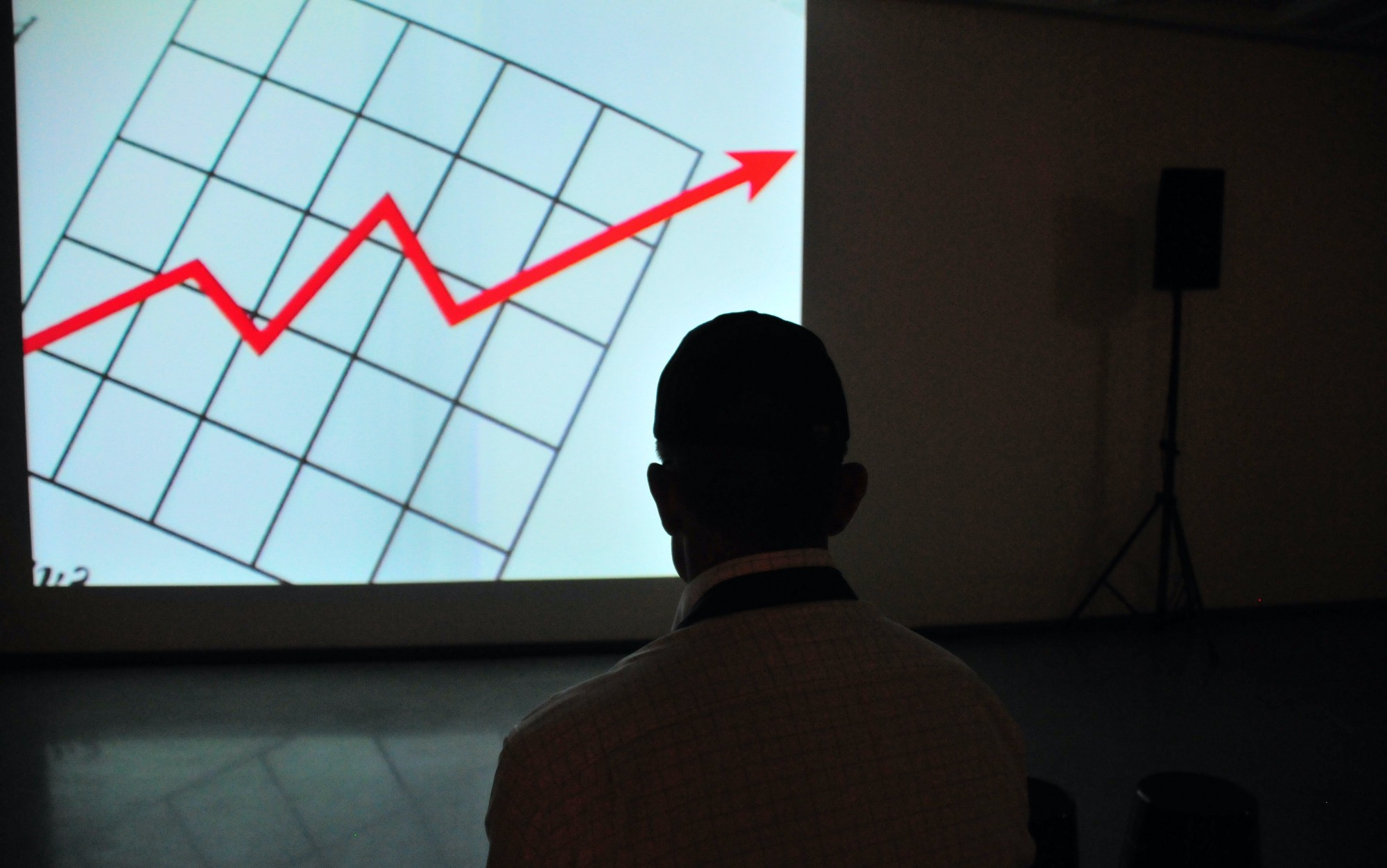 A man is looking at a screen showing a graph with a red line trending up.