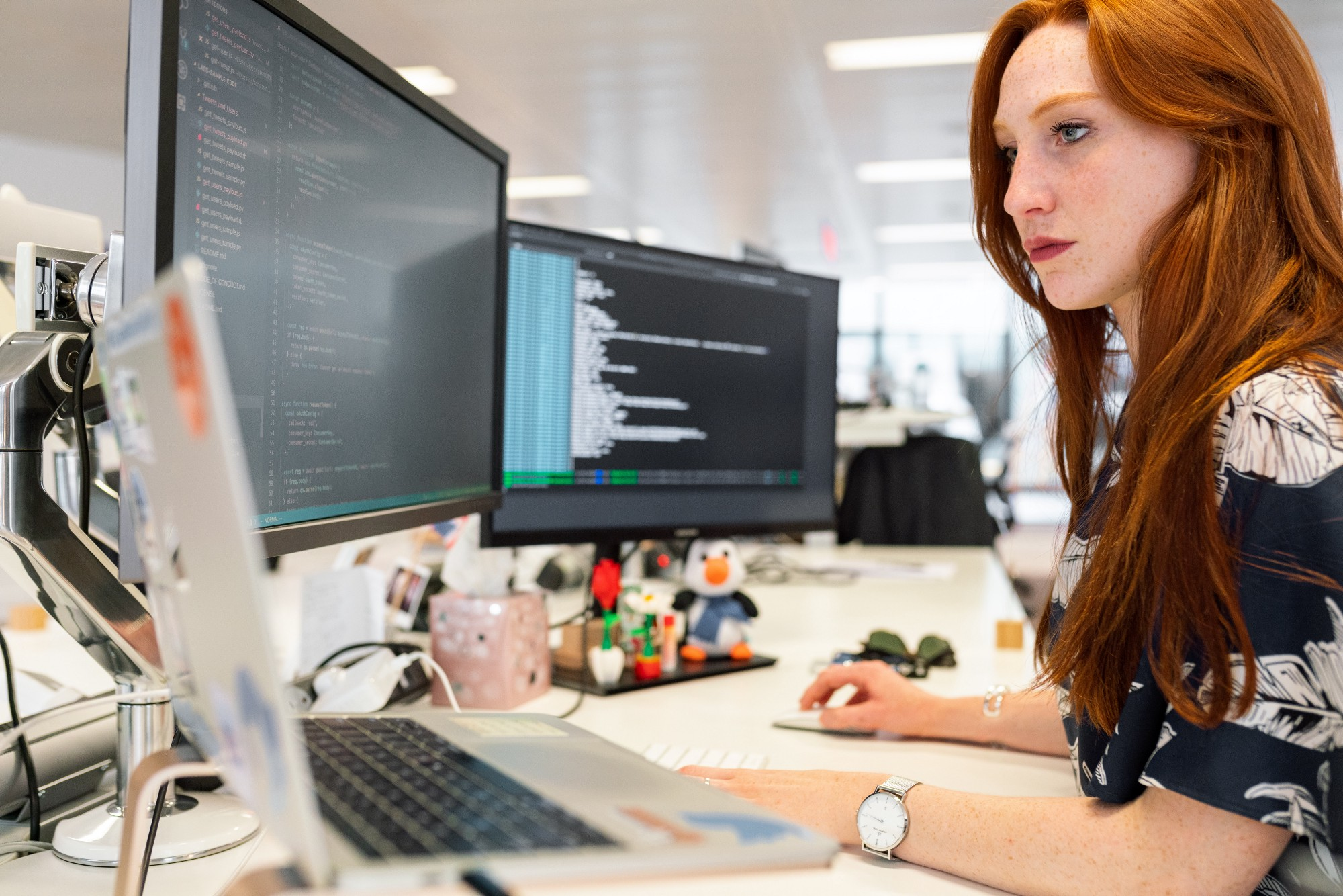 Woman sitting at desk in front of screens with computer code