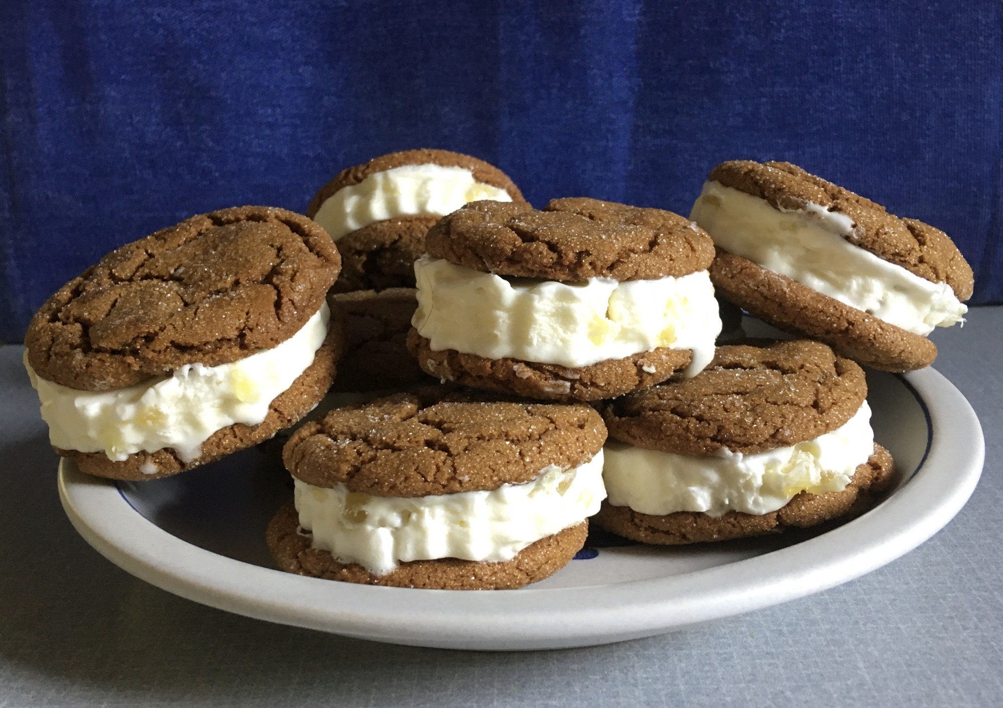 A white platter piled high with ice cream sandwiches made with ginger cookies.
