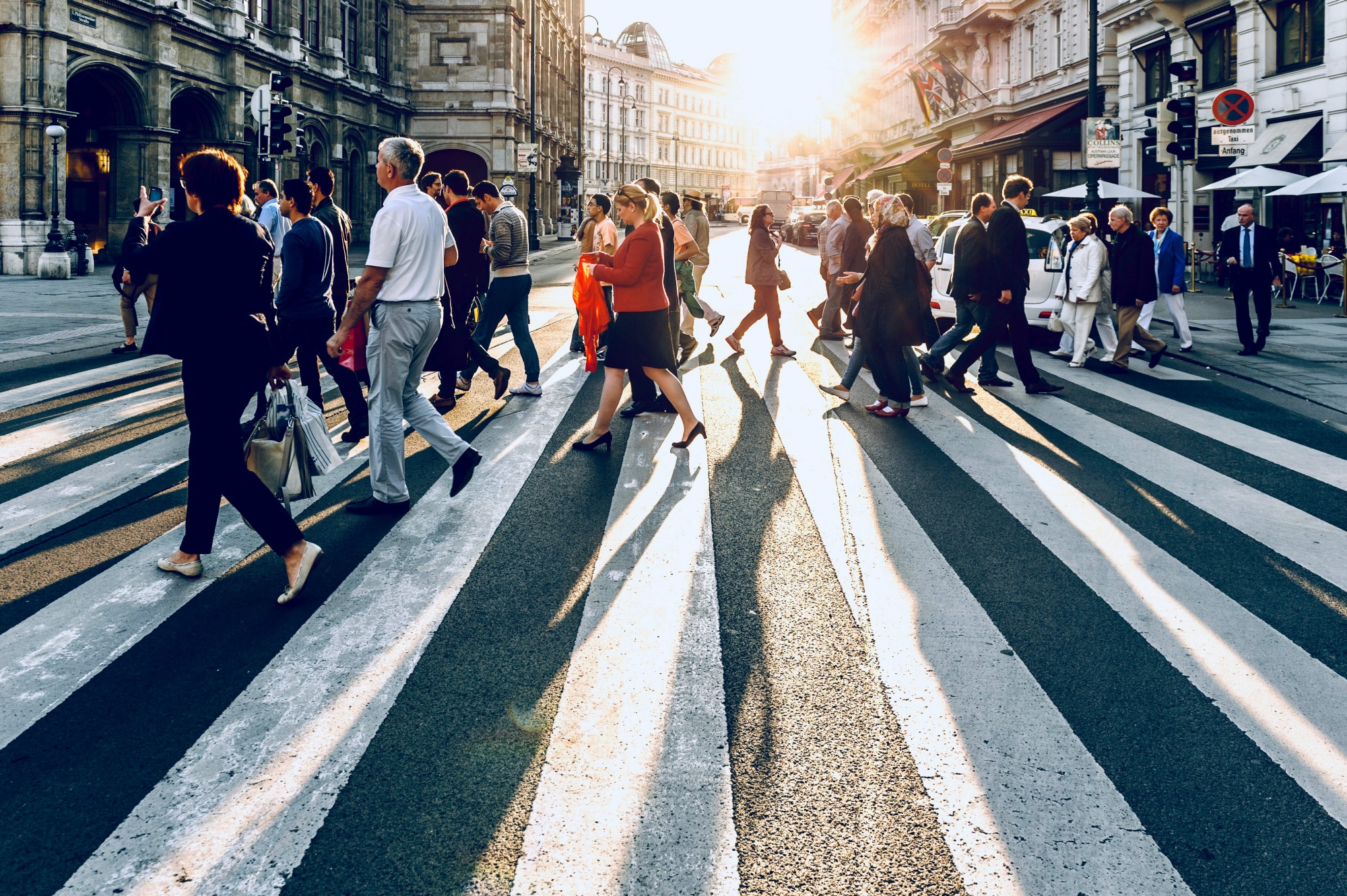 a crowd of people crossing the street in a big city