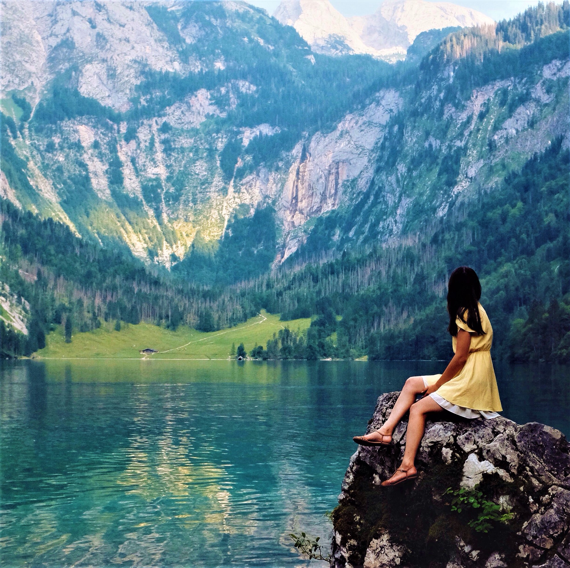 girl with long dark hair wearing yellow dress sitting on boulder looking out over lake and mountains
