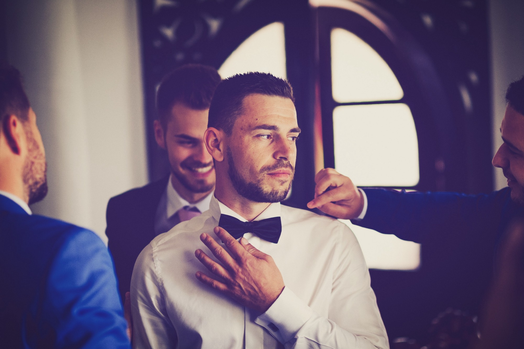 A man in a wedding suit looking aside while surrounded by friends