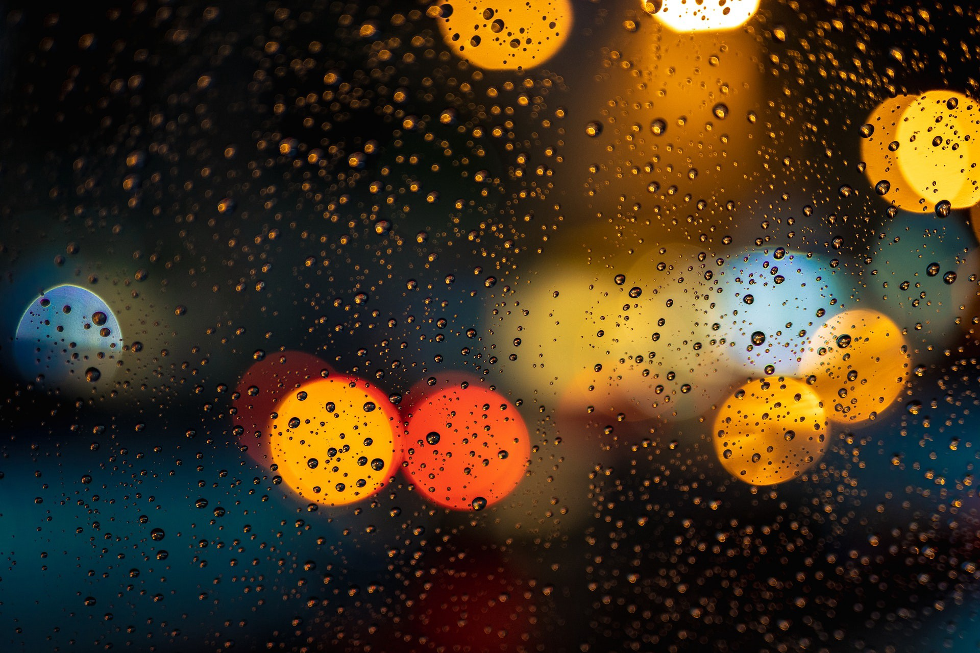 Water droplets on surface against lights in the background