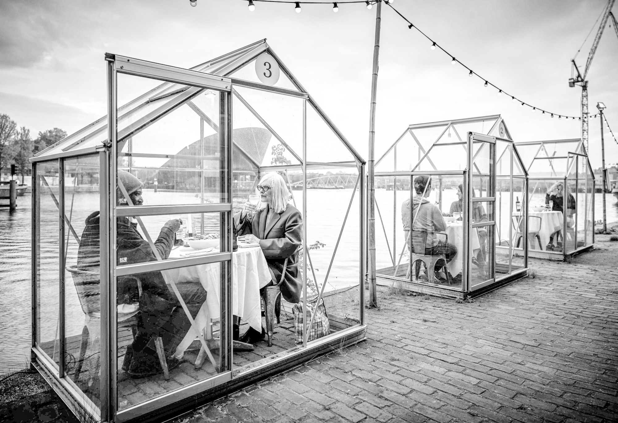 Guests of ETEN sitting inside greenhouses that the restaurant has converted into isolated dinning pods.