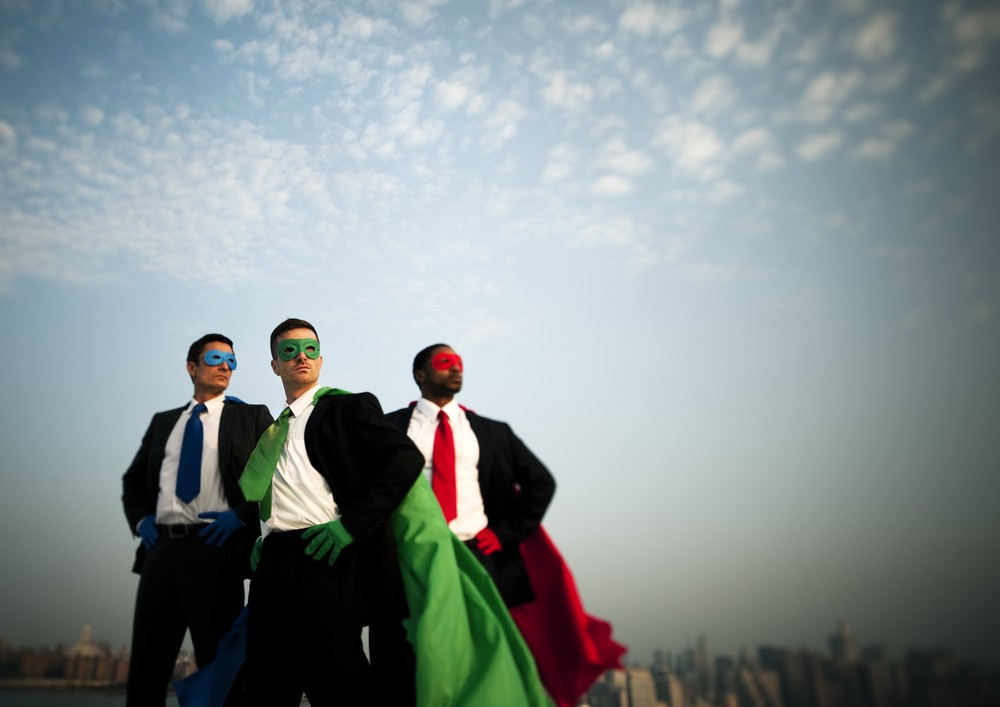 Image of three business professionals in suits but with superhero-style masks and capes