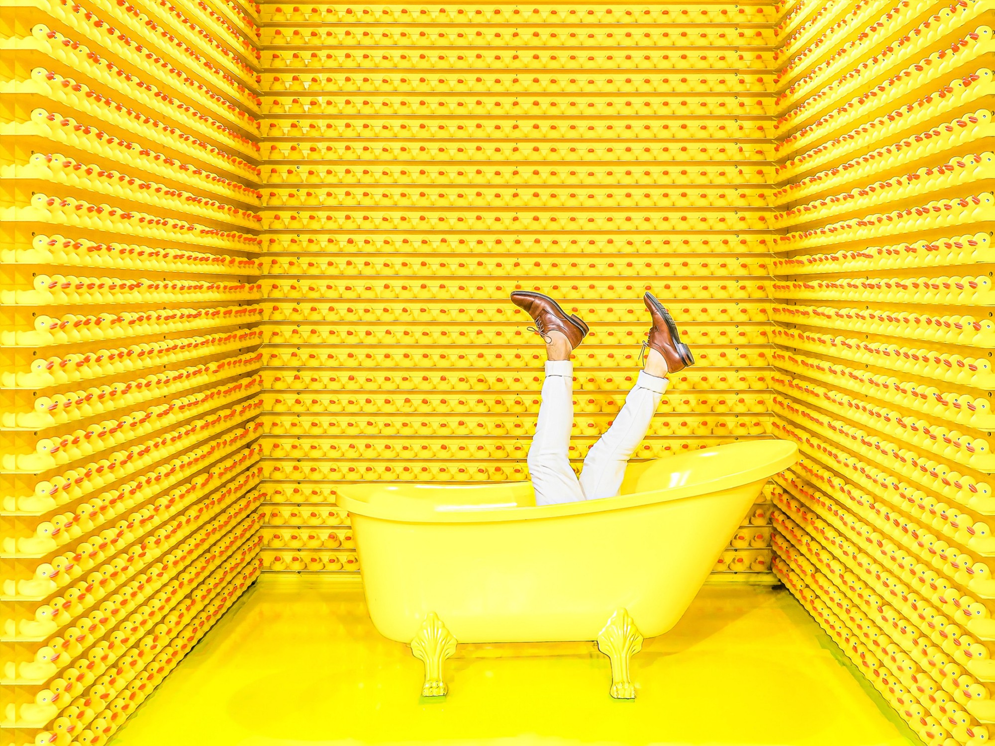 Man comically drowning in yellow bathtub surrounded by walls of rubber duckies.