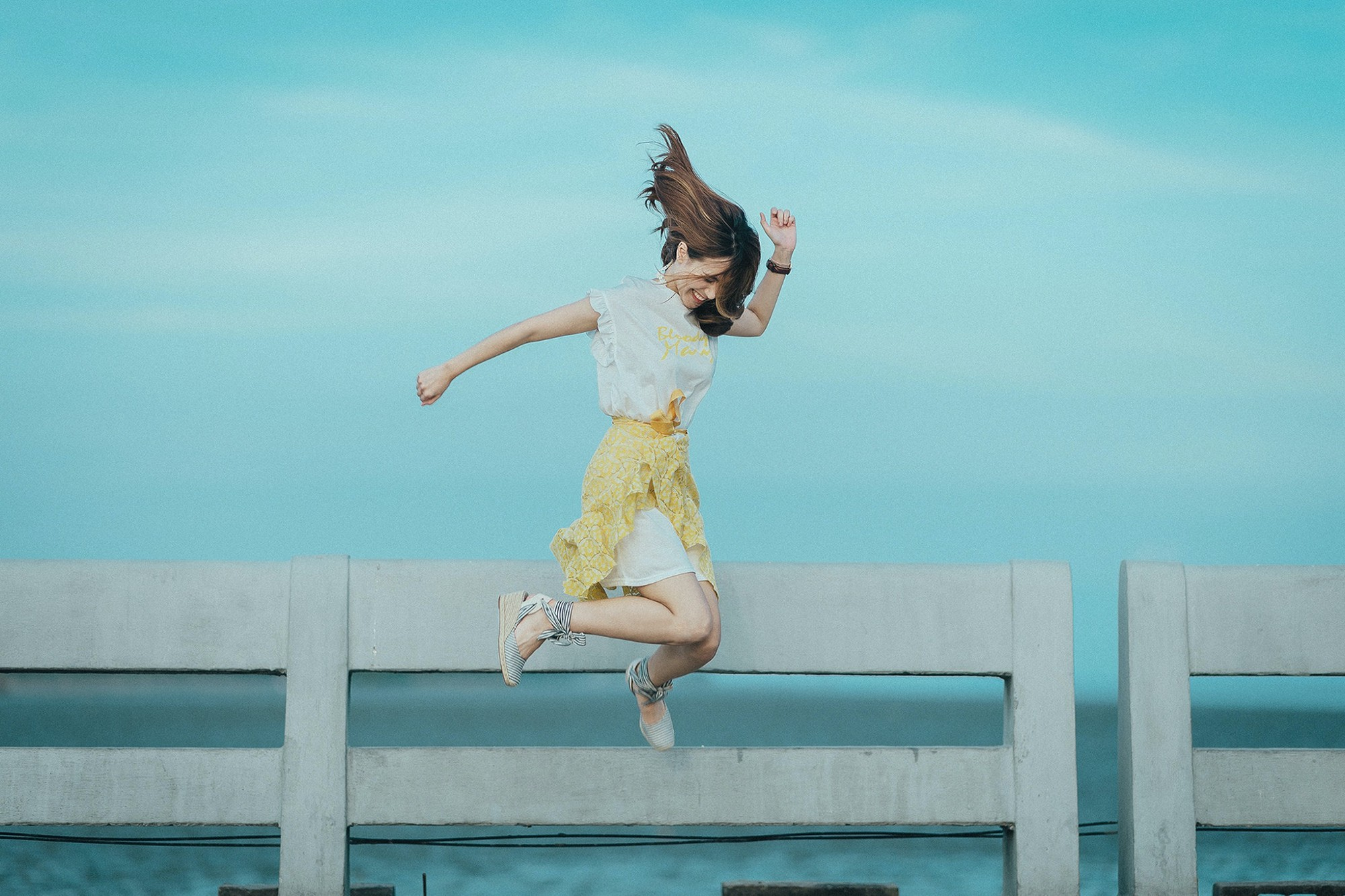 A young woman with a yellow skirt and white t-shirt jumping high against a blue sky and concrete fence.