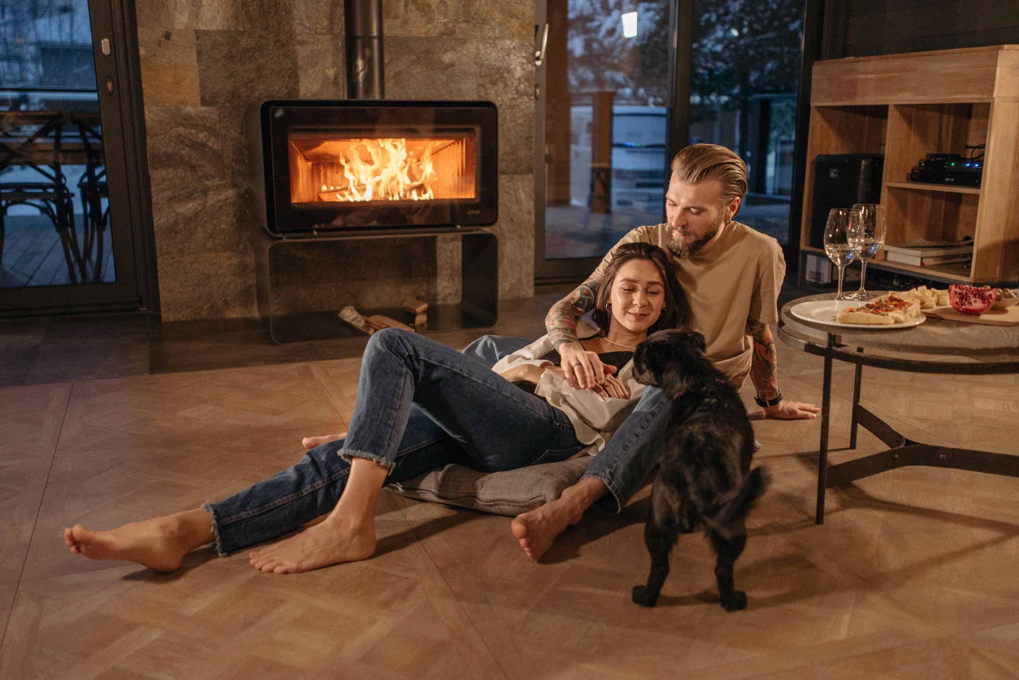 A couple with their dog sitting by the fireplace during a snowy late evening