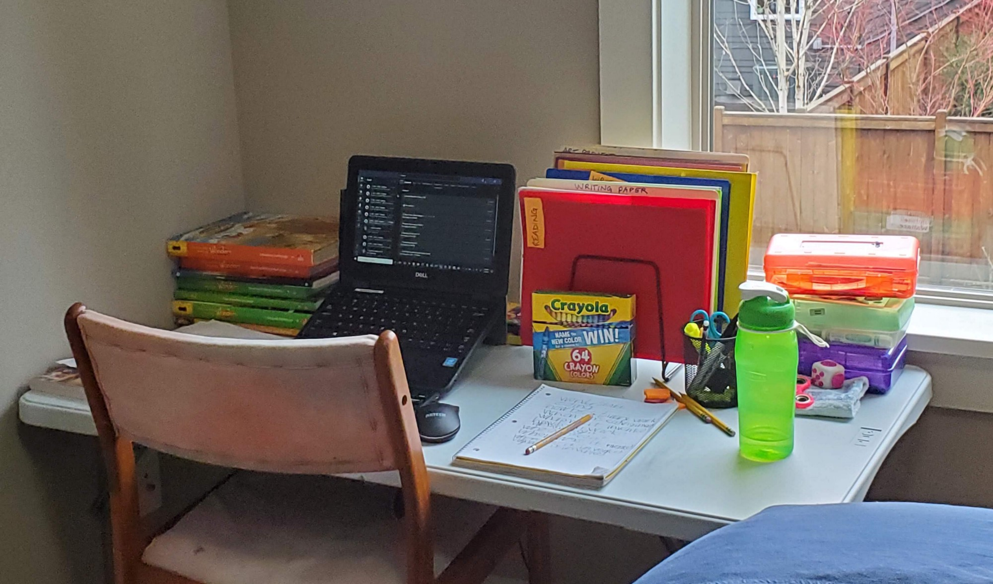 A folding table in a guest bedroom with a laptop, folders, and other school materials arranged on it.