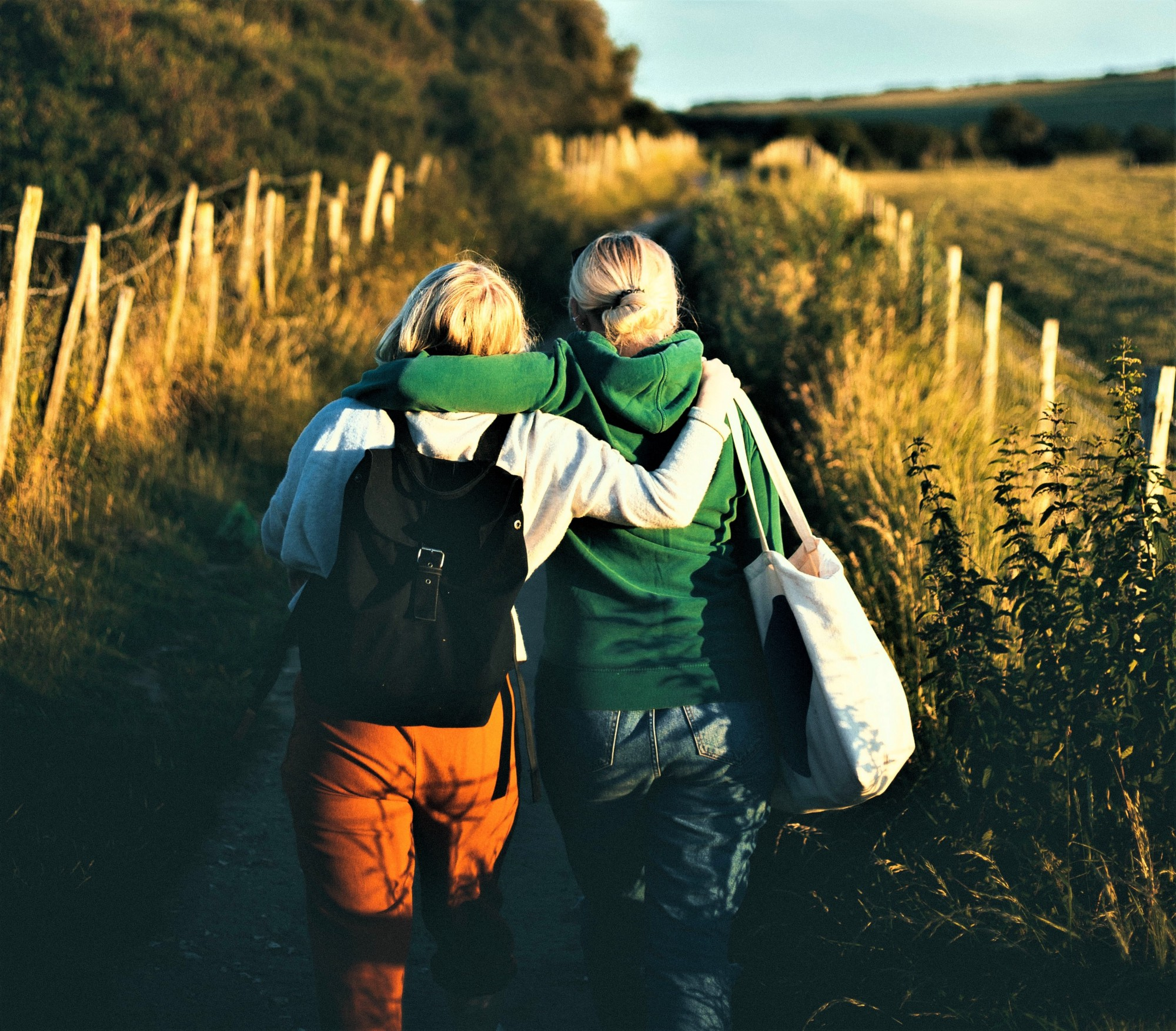 back view of two people with blonde hair wearing backpacks walking along a country road
