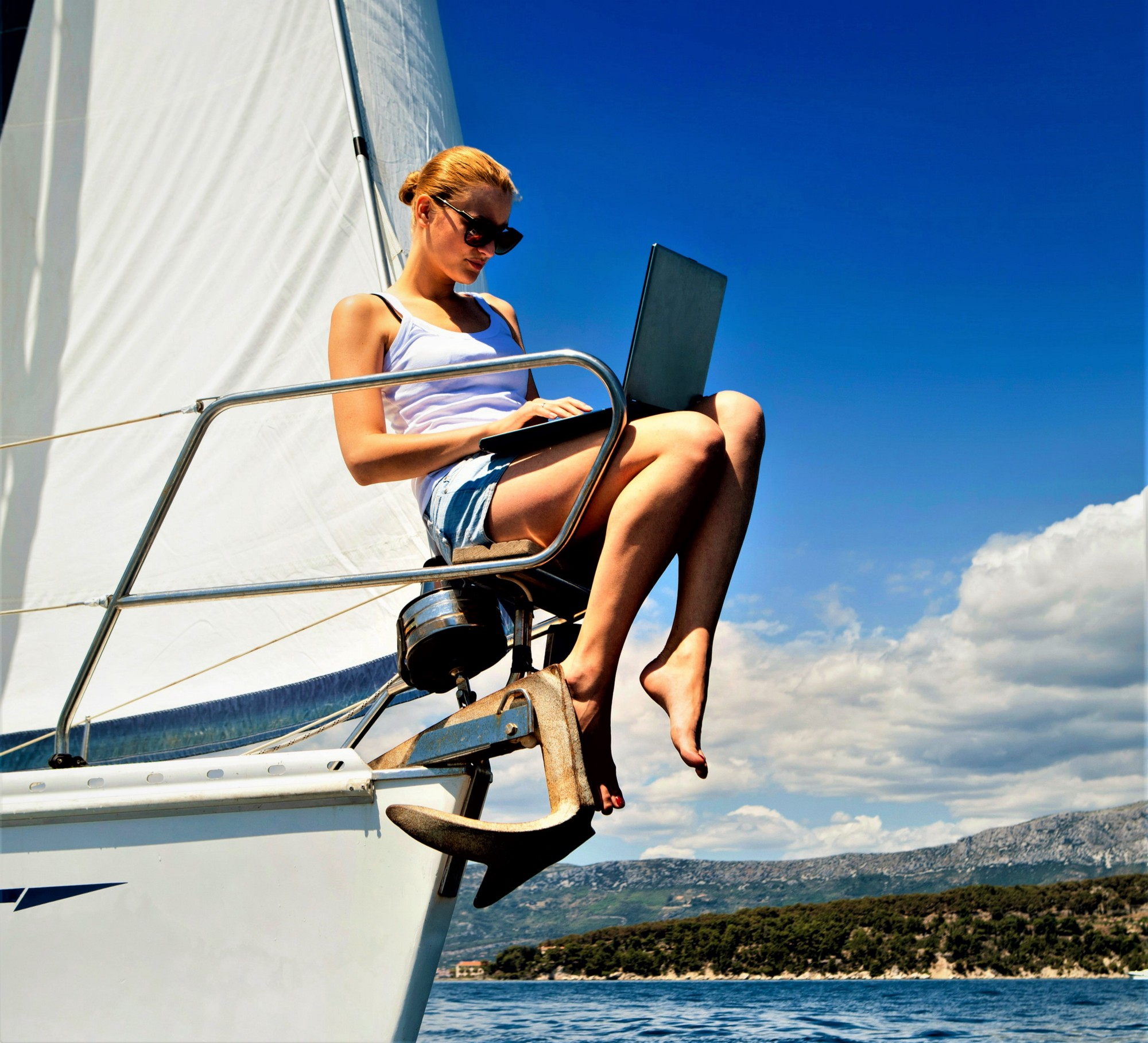 girl with blonde hair wearing white t-shirt and blue shorts sitting on front end of sailboat with computer in her lap