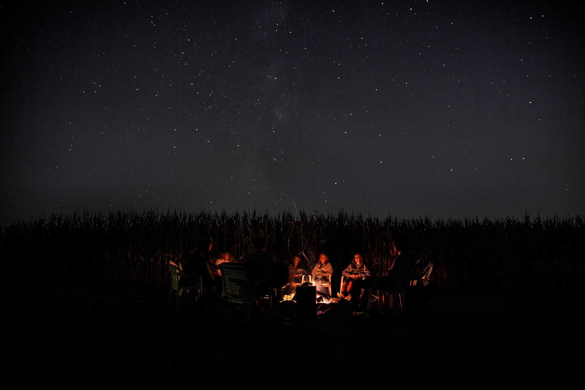 people around a campfire under the stars