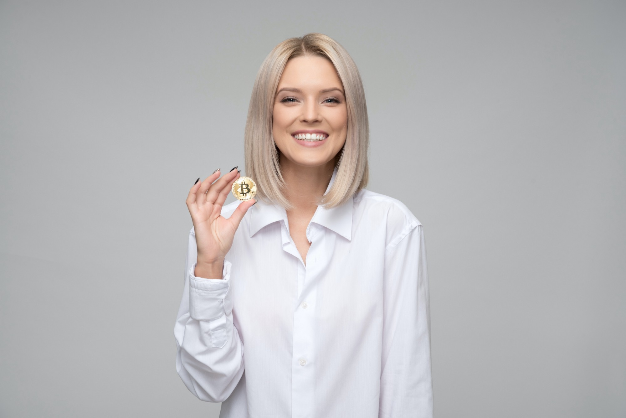 Woman smiling holding a Bitcoin cryptocurrency