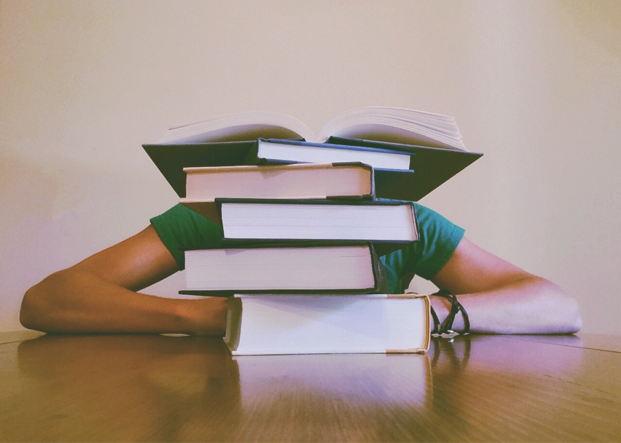 Person hidden behind stack of books