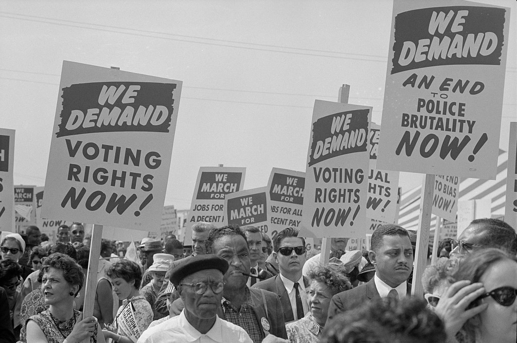 """black and white photo of marchers holding signs that say """"We demand voting rights now!"""""""