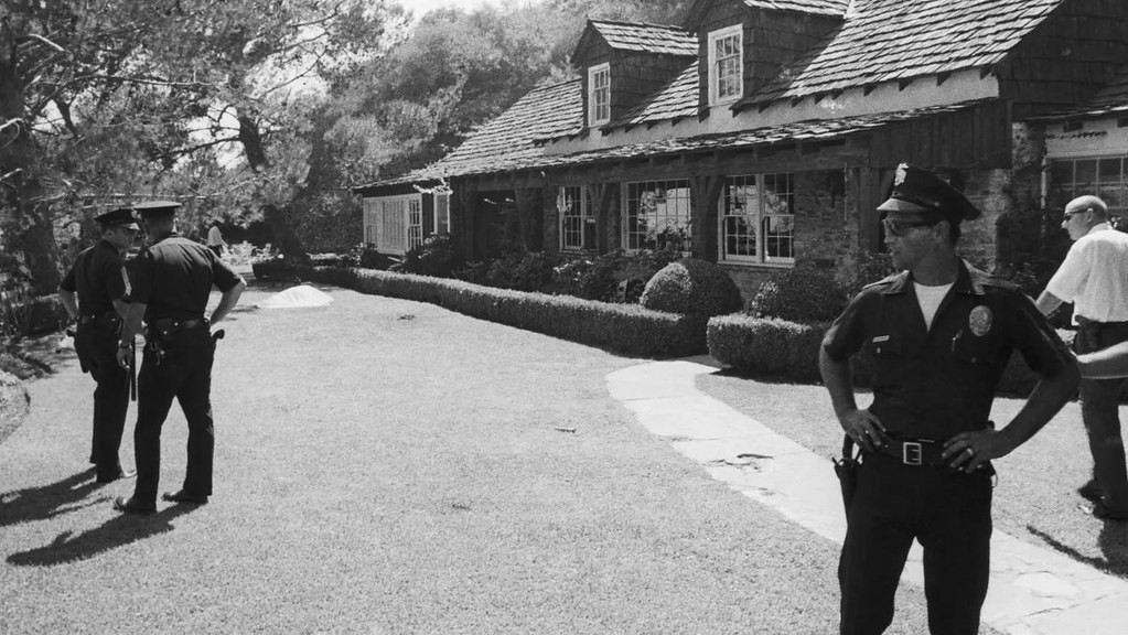 Policemen stand outside the Hollywood home of Roman Polanski and Sharon Tate at 10050 Cielo Drive now a crime scene