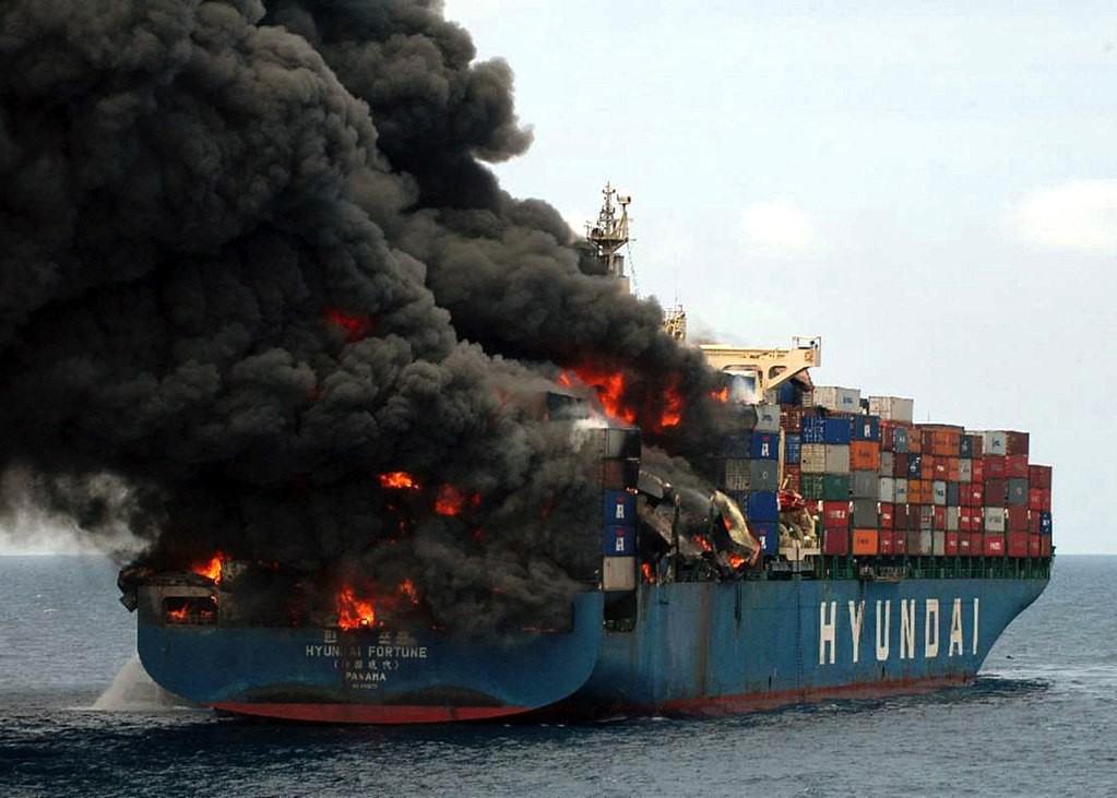 The container ship Hyundai Fortune on fire with dark pillows of smoke.