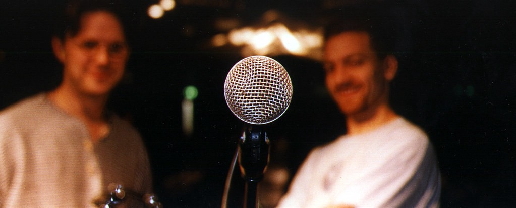 A close-up of a microphone, with two blurry listeners in the background.