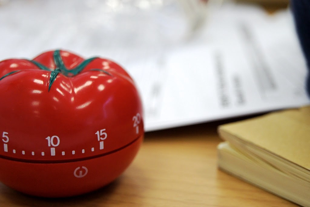 Tomato timer in front of some out-of-focus papers
