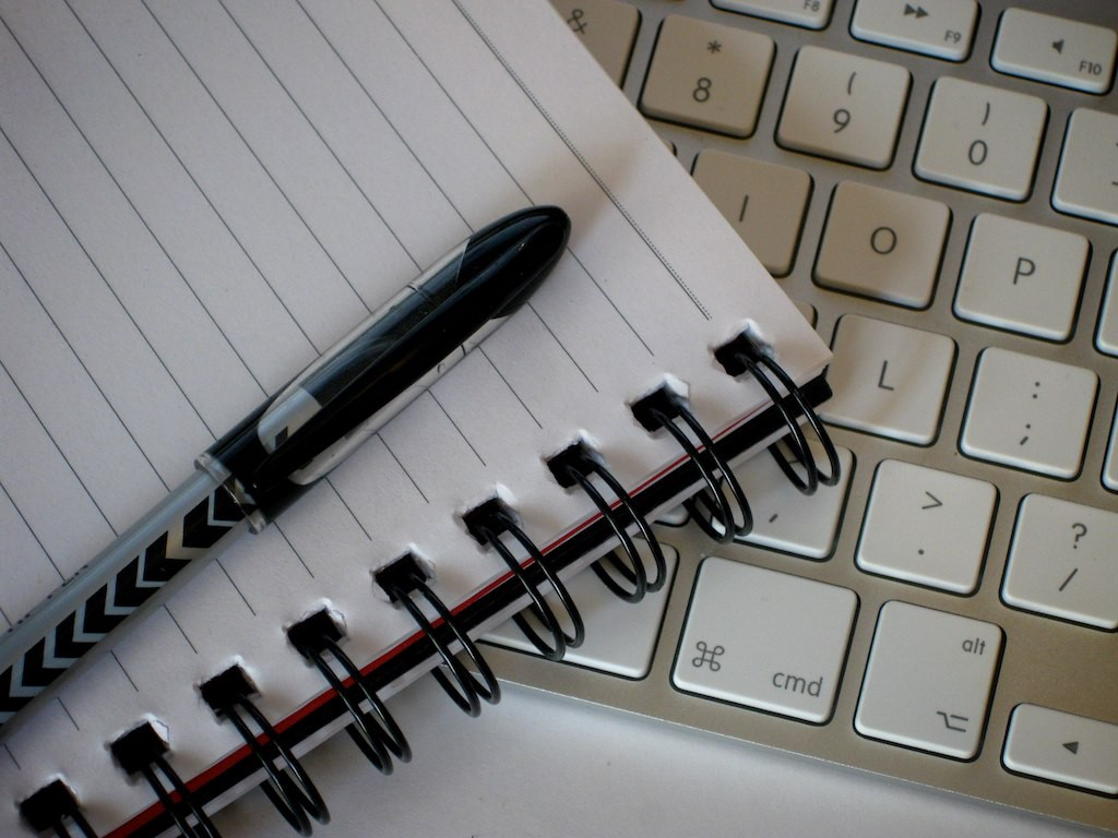 A pen sitting on a spiral notebook, sitting on a keyboard.
