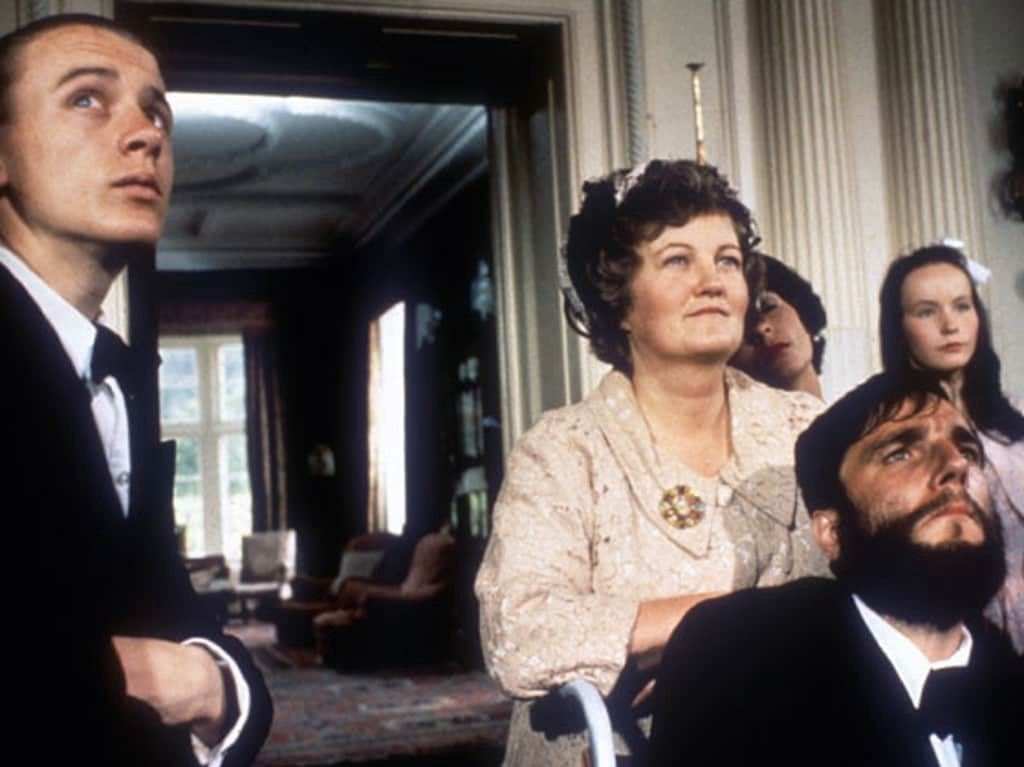 """A still from the film """"My Left Foot."""" A man in a suit stands on the left side while a woman leans on the wheelchair of the main character, Christy Brown, played by Daniel Day-Lewis."""