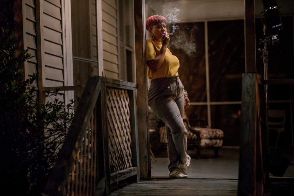 A woman with pink hair smoked a cigarette at night on a back porch.