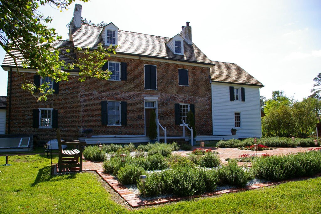 Brick house with small garden in the front with bench