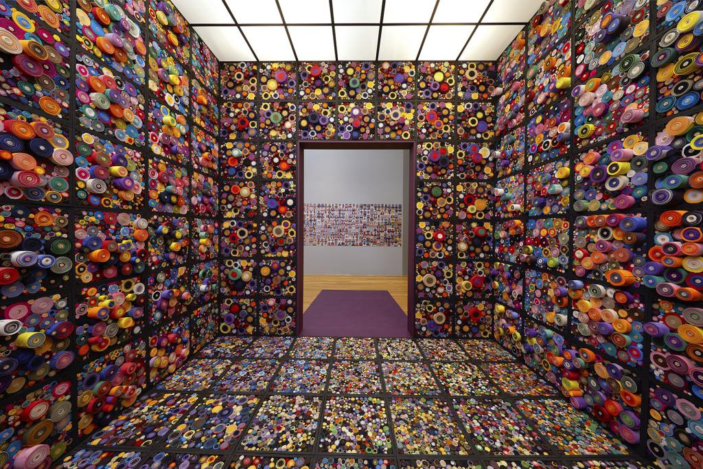 An installation space features walls and floors made of grids filled with scrolls of colorful fabric.