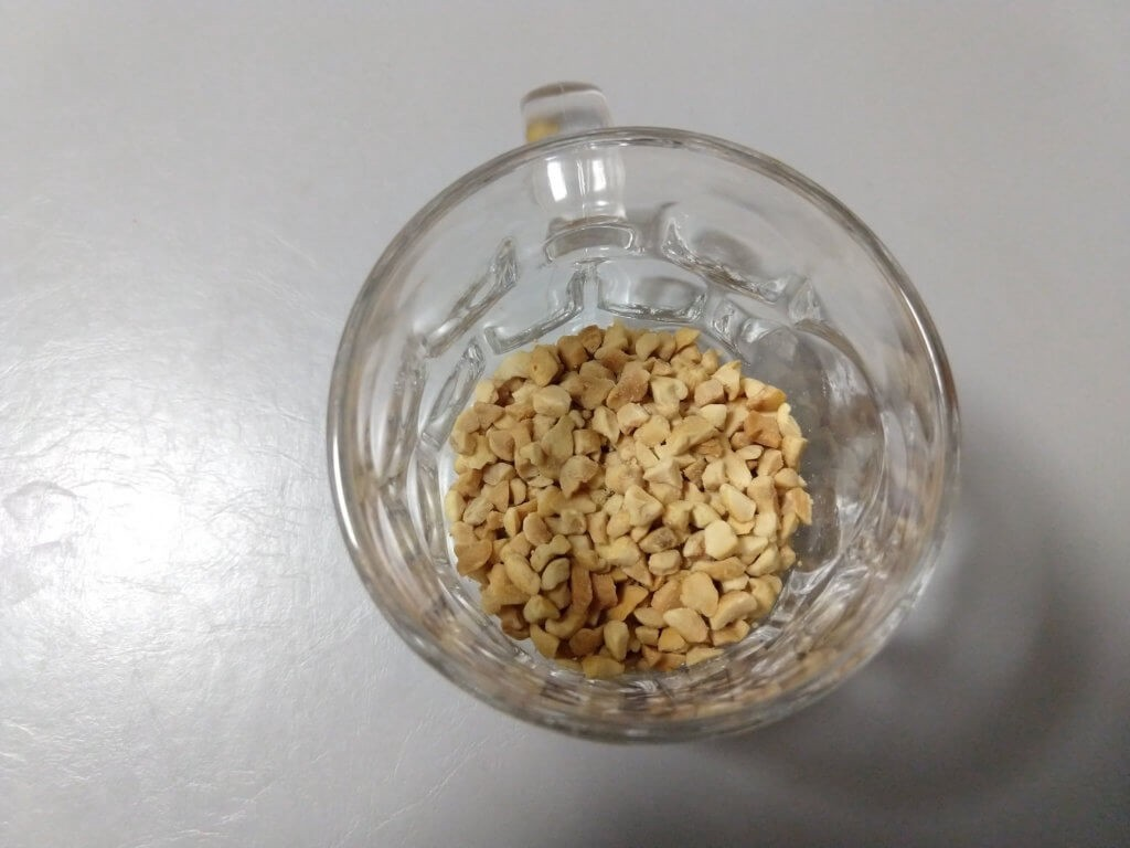 Top view of a drinking glass containing a small amount of crushed peanuts.