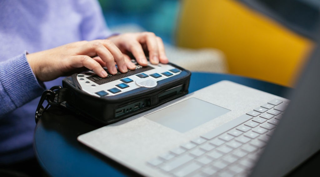 Someone using a braille keyboard on a computer