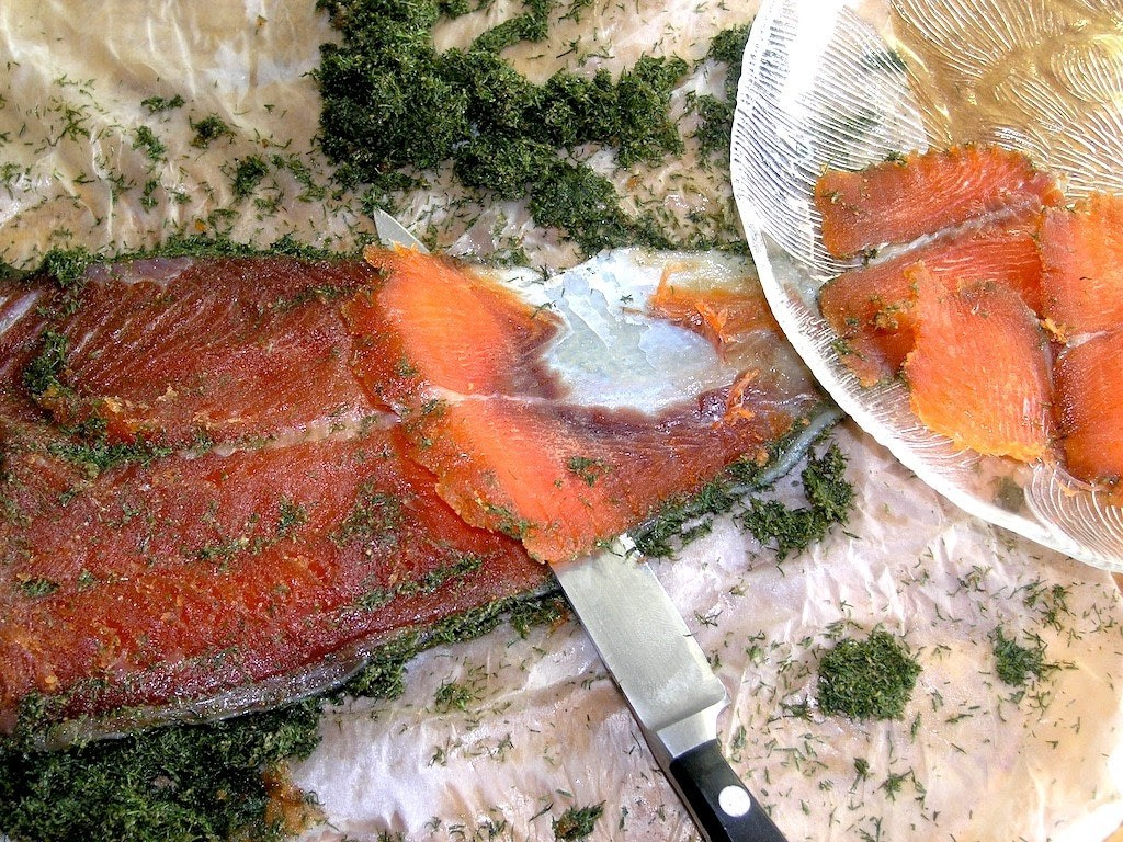 Salmon being sliced on a cutting board next to a glass bowl of paper-thin slices of fish.