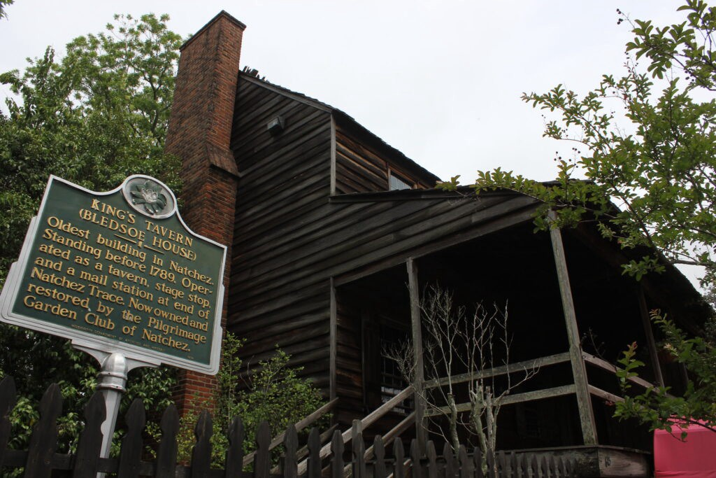Building made of dark wood with brick chimney, green King's Tavern sign