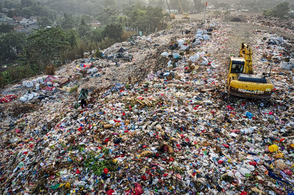 A yellow excavator in a garbage mountain