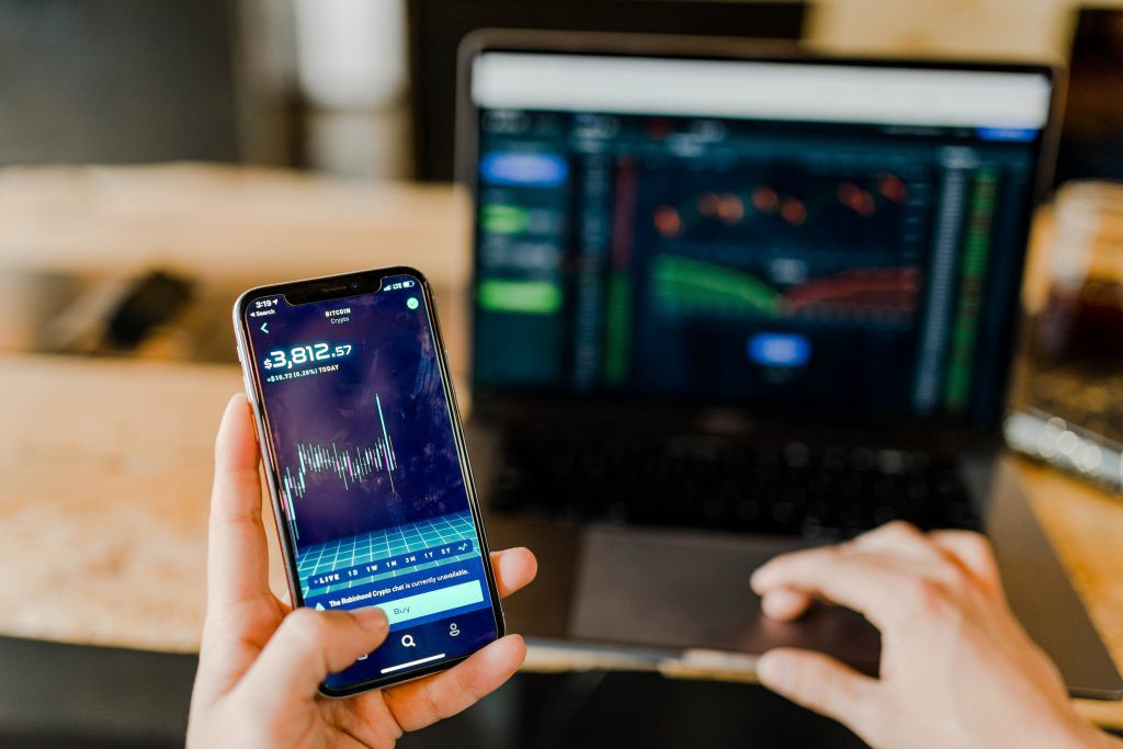 stock charts on phone and laptop