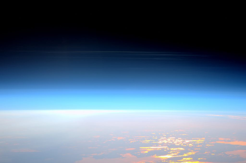 Noctilucent clouds shimmer to the horizon, in this picture of Earth taken from the ISS, which also shows the upper atmosphere changing from bright blue to dark blue to the black of space.