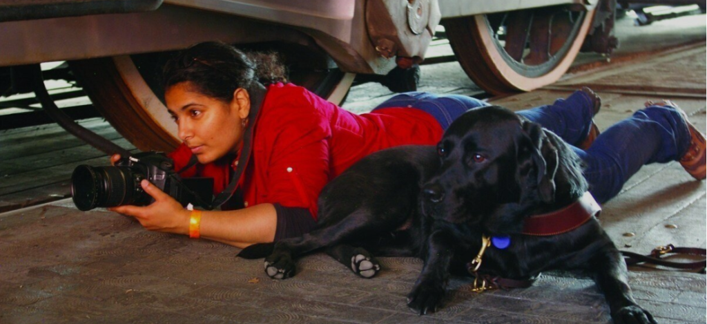 A woman with black hair pulled back & brown skin lies on her stomach holding a camera. Her black dog lies next to her.