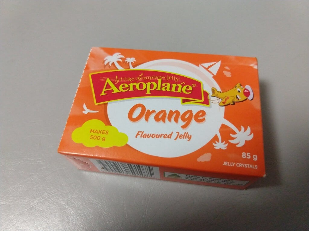 An 85 gram package of orange-flavoured Aeroplane Jelly.