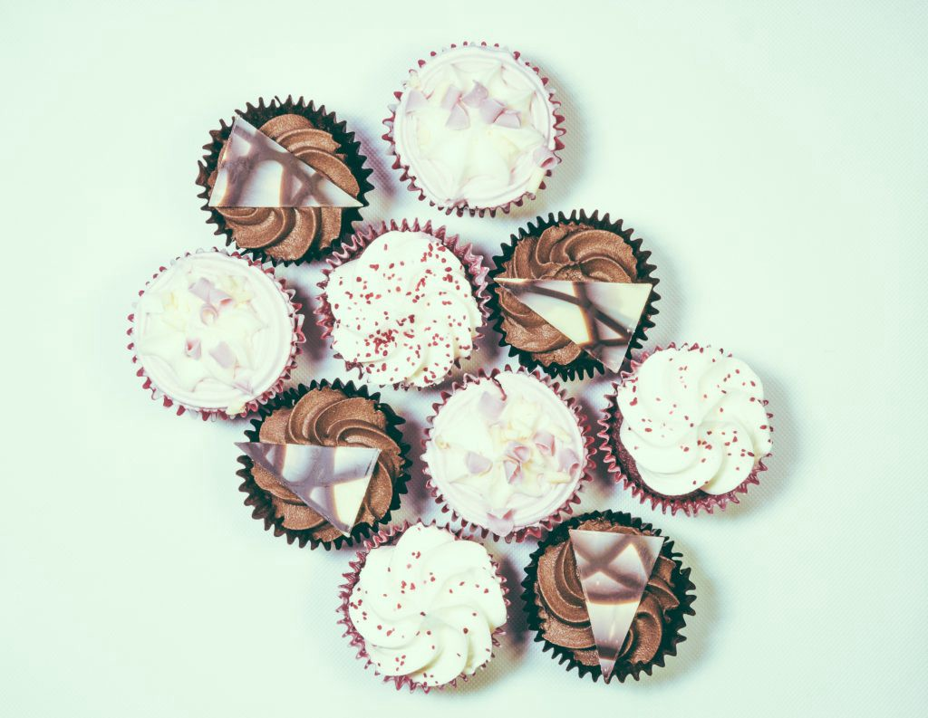Numerous brown and white cupcakes.