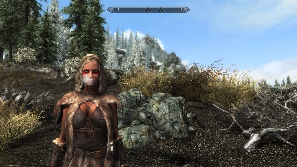 Dragonborn standing on a hill side with mountains and trees in the background.