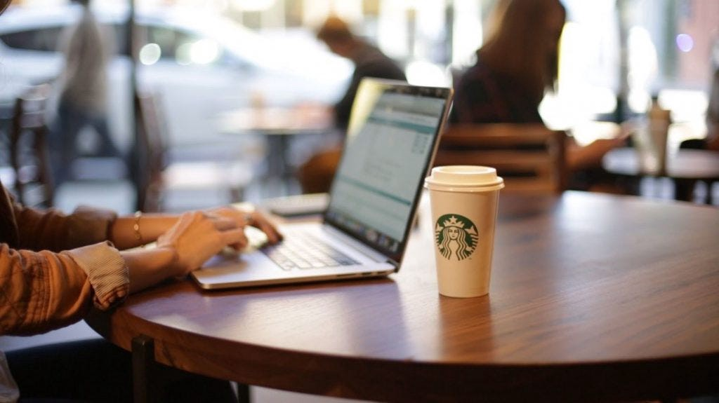Solo customer, sitting at a round table at Starbucks with a laptop and coffee by their side.