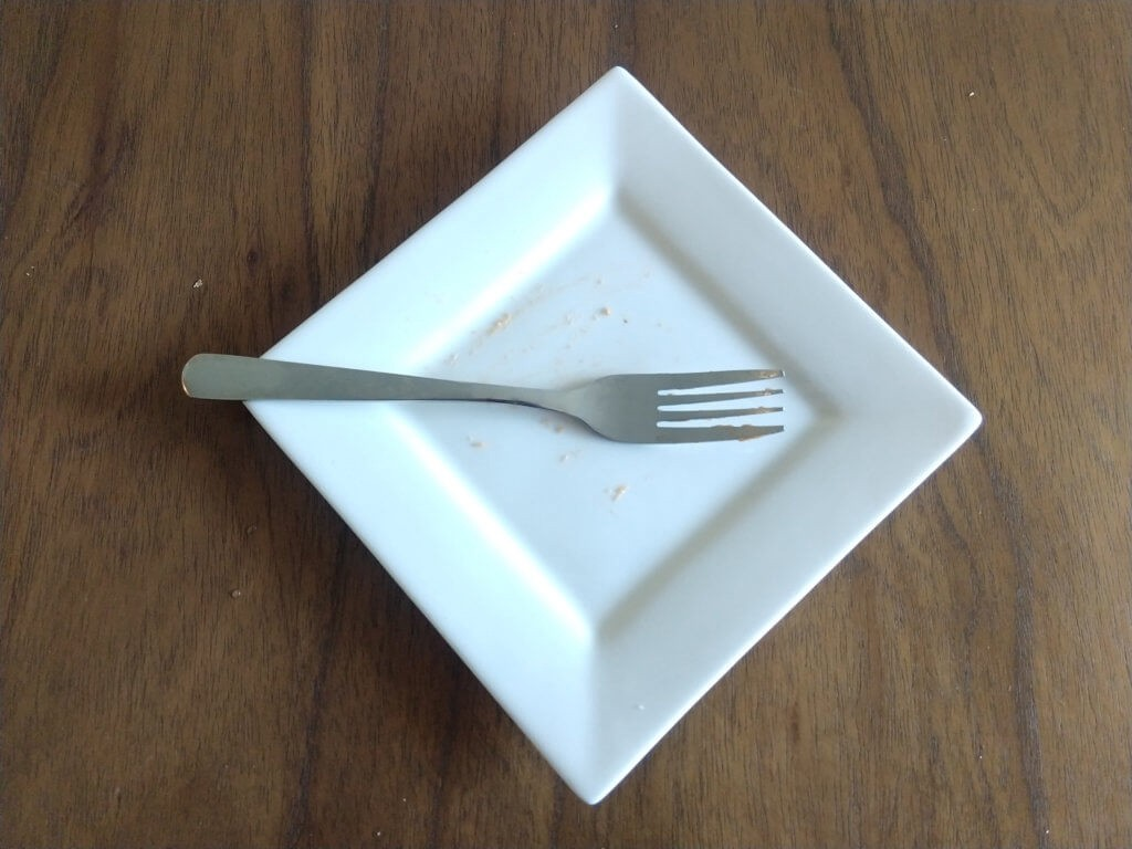 An empty white plate, apart from a few crumbs, on a table with a fork resting on top of it.