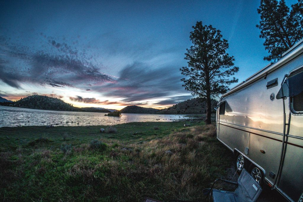 RV parked by a lake at sunset