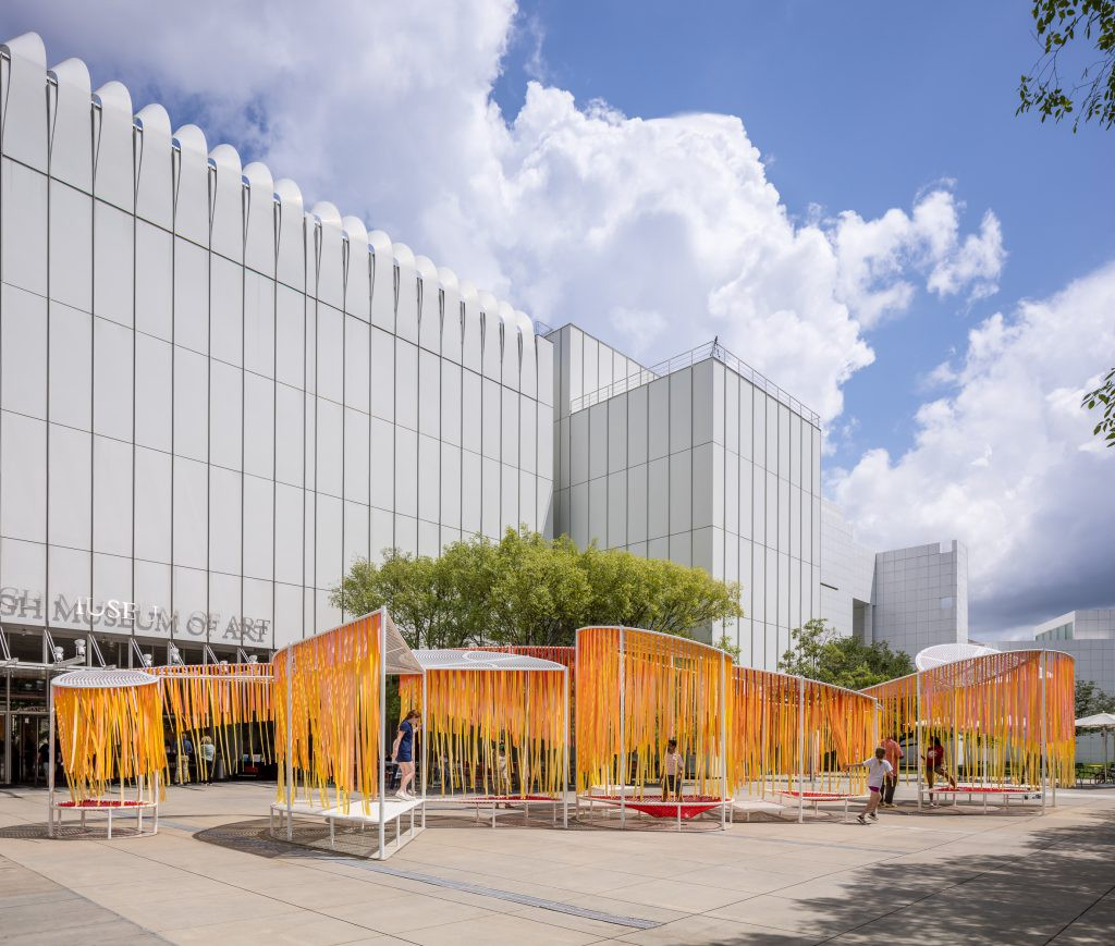 A curvilinear, outdoor installation space with orange and red hanging strands seen under a blue sky.