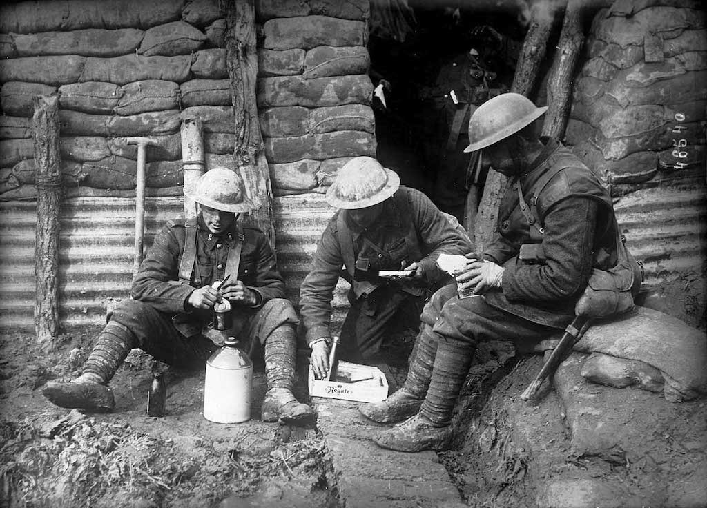 A photograph of three allied soldiers sitting together for a meal in a trench wearing camouflage uniforms and metal helmets.