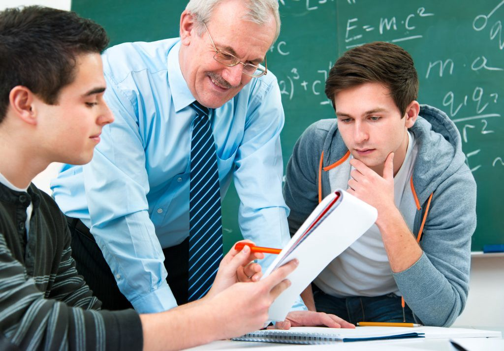 Image of a teacher assisting two students
