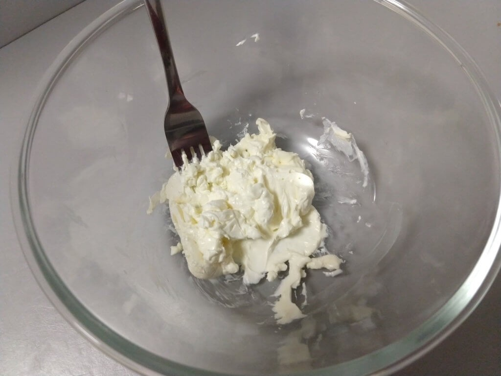 A glass bowl with a portion of cream cheese in the bottom, with a fork sticking out of it.